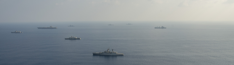 INDIAN OCEAN (Oct. 16, 2015) Ten ships and submarines from the Indian, Japanese and U.S. navies maneuver into a close formation during Exercise Malabar 2015. Malabar is a continuing series of complex, high-end war fighting exercises conducted to advance multi-national maritime relationships and mutual security. The aircraft carrier USS Theodore Roosevelt (CVN 71) is operating in the U.S. 7th Fleet area of operations as part of a worldwide deployment en route to their new home port in San Diego to complete a three-carrier homeport shift. (U.S. Navy photo by Mass Communication Specialist 2nd Class Chris Brown/Released); Public Domain